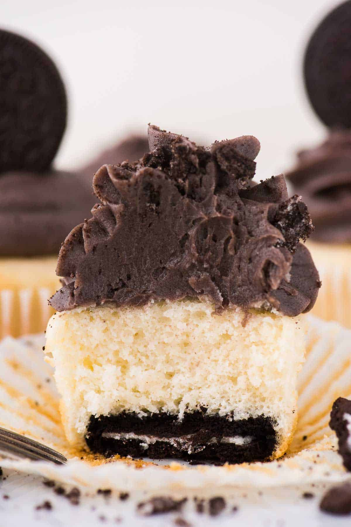 vanilla oreo bottom cupcake cut in half on white background