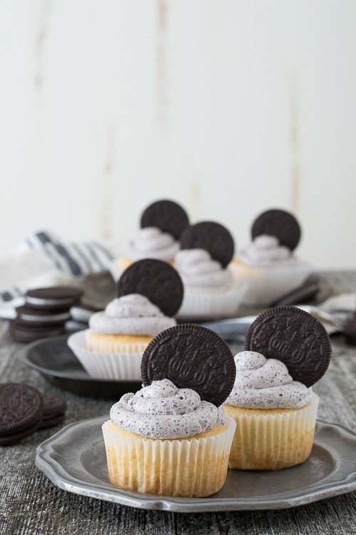 Two Oreo Cupcakes on a small silver serving plate.