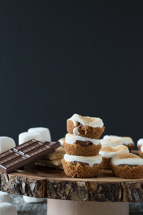 3 s'mores bites in a stack on round wood cake stand