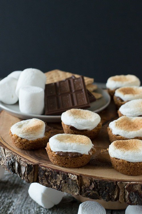 s'mores bites with toasted marshmallow tops on round wood cake stand