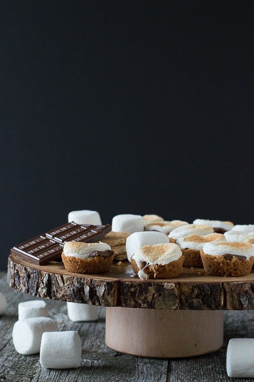 s'mores bites on round wood cake stand with marshmallows in foreground on dark background