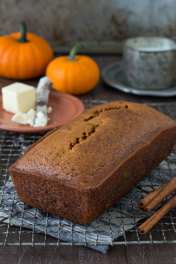 Large loaf of homemade Starbucks Pumpkin Pound Cake on a cooling rack with two cinnamon sticks.