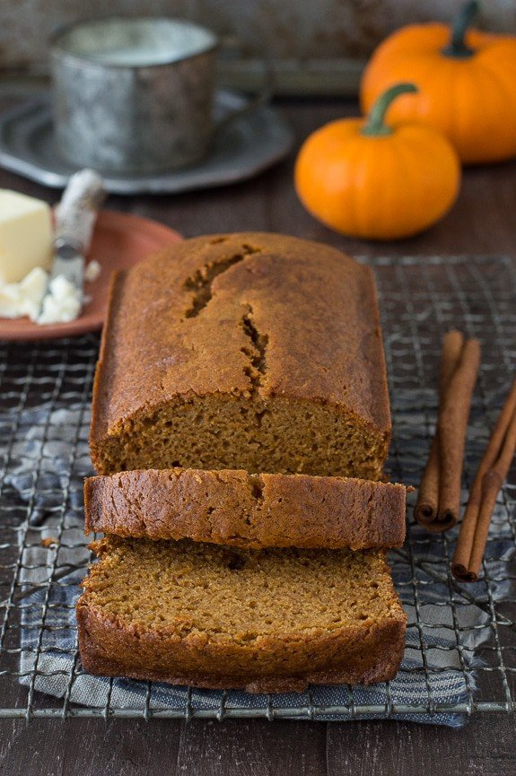 Sliced easy Starbucks Pumpkin Pound Cake on a cooling rack with two delicious cinnamon sticks.