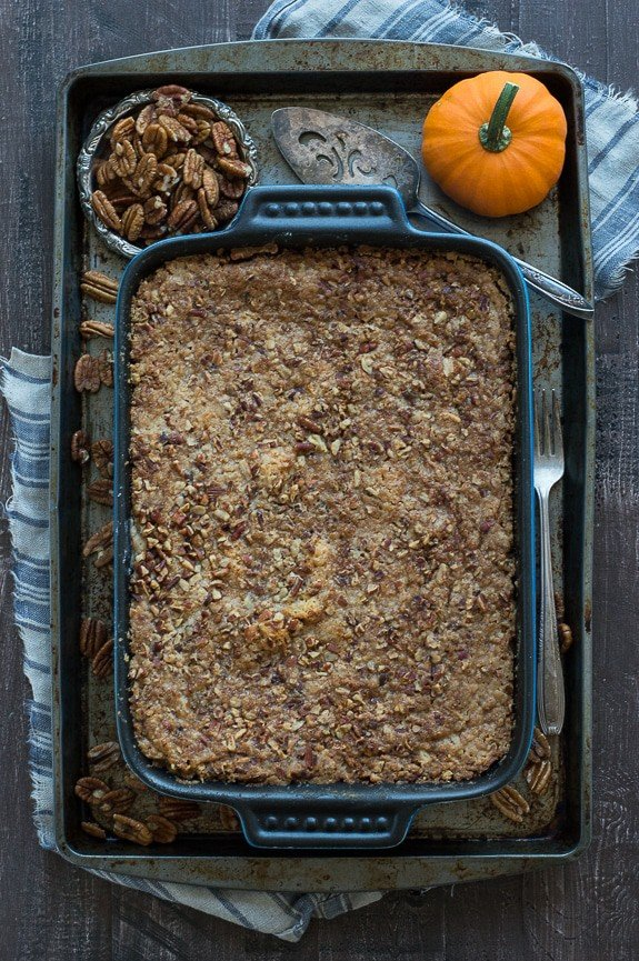 Blue casserole dish with Pumpkin Dump Cake a baking dish surrounded by a small cup of pecans and small pumpkin.