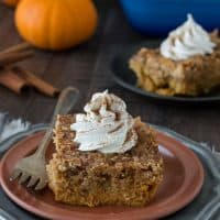 Small slice of Pumpkin Dump Cake on a brown serving plate with a silver fork.