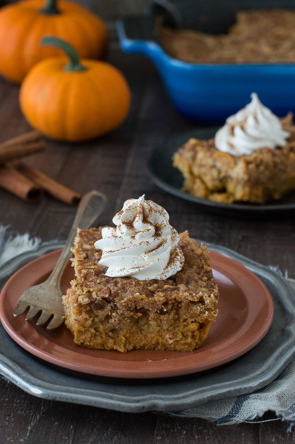 Slice of Pumpkin Dump Cake with whipped cream on top of a brown serving plate with a silver fork.