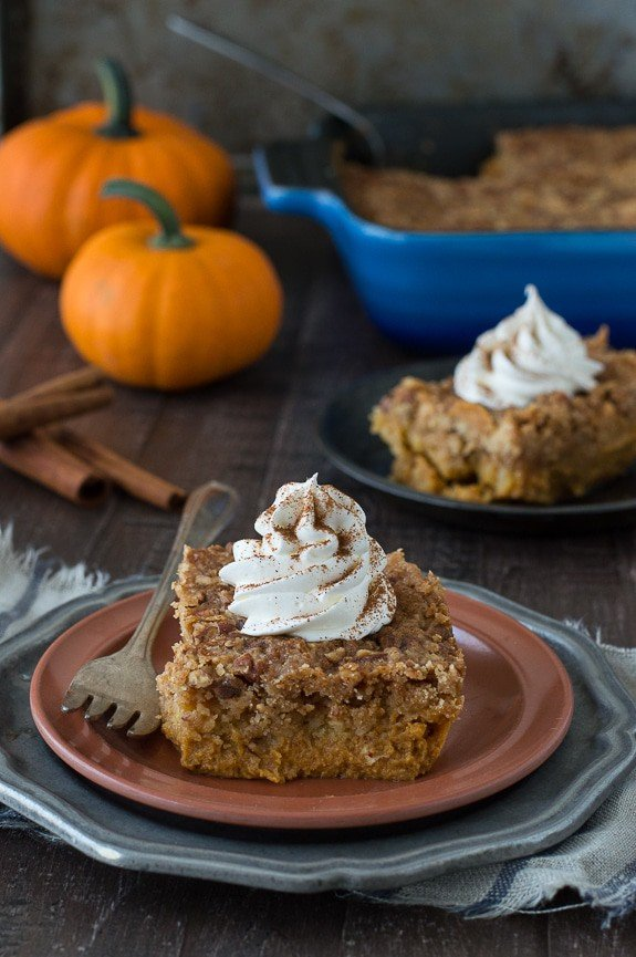 Delicious slice of Pumpkin Dump Cake with whipped cream on a brown serving plate with a silver fork.