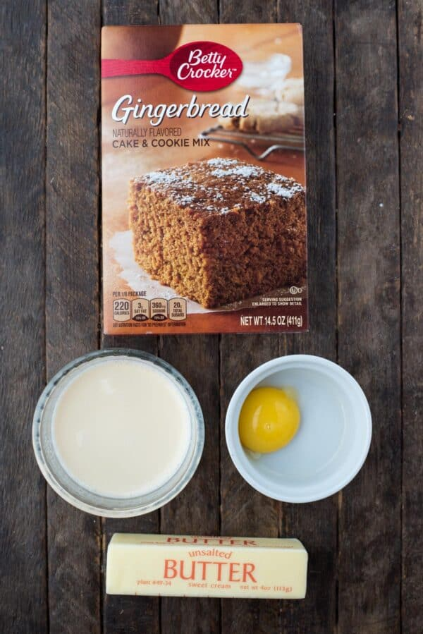 ingredients to make gingerbread brownies - gingerbread cake mix, evaporated milk, egg yolk, and stick of butter