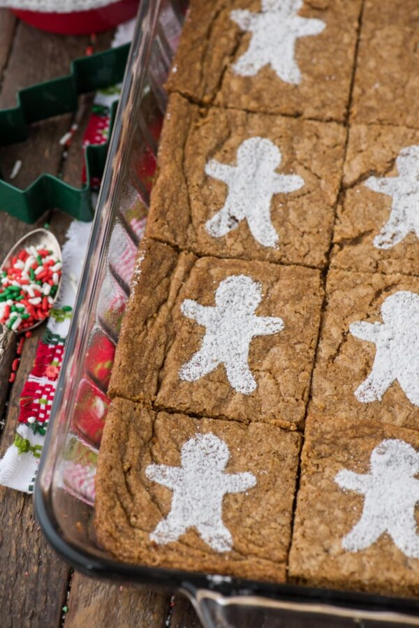 gingerbread brownies dusted with powdered sugar gingerbread men in glass 9x13 inch pan on wood background