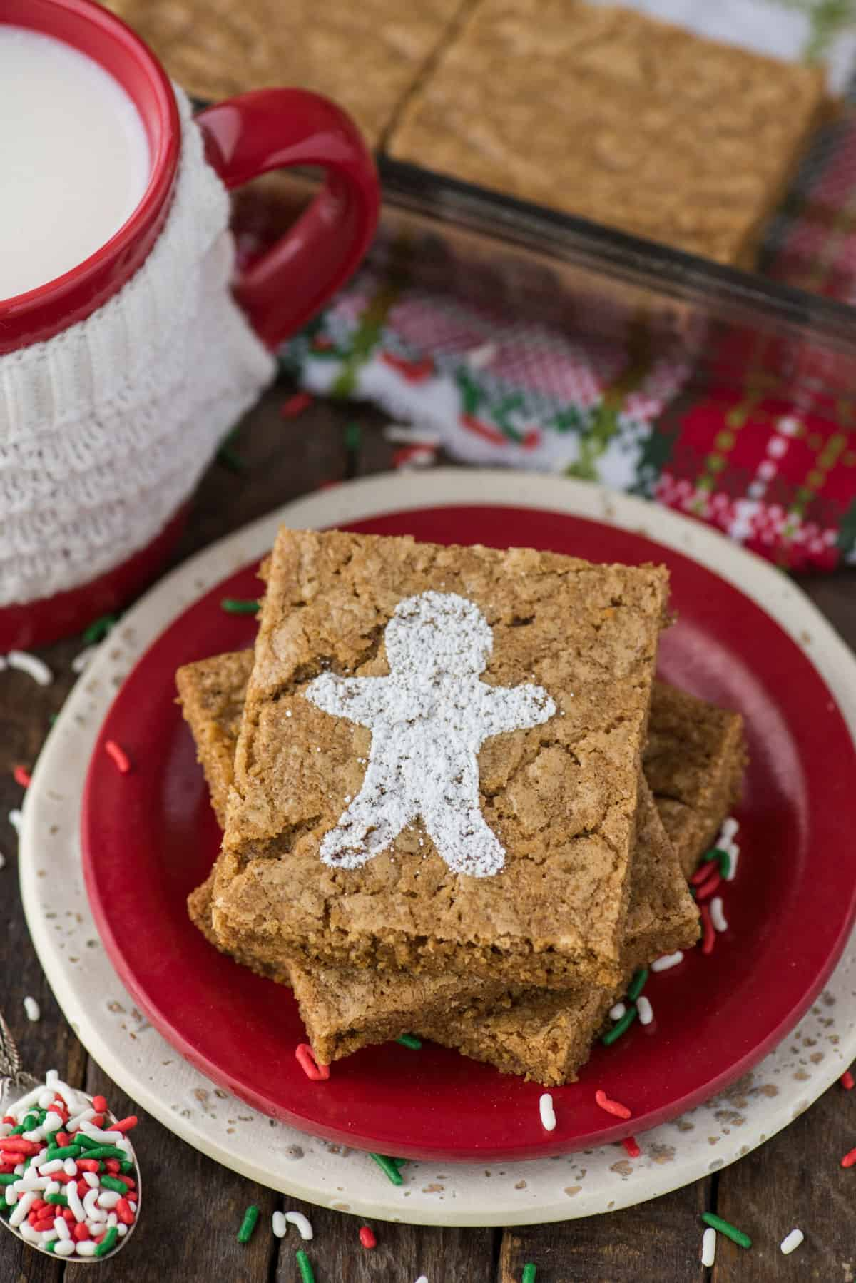 gingerbread brownies dusted with powdered sugar gingerbread men on red plate on wood background