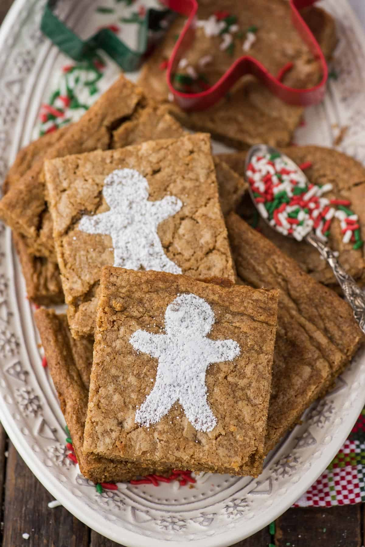 gingerbread brownies dusted with powdered sugar gingerbread men on a white platter