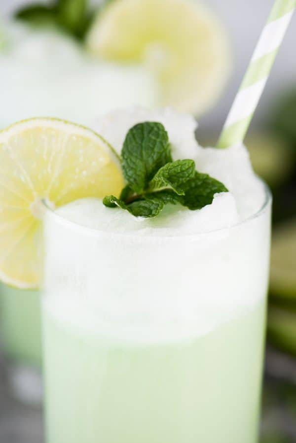 lime sherbet float in glass cup with lime slice, mint leaves and green straw