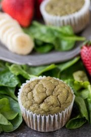 One healthy Green Monster Smoothie Muffin surrounded by spinach on a table.