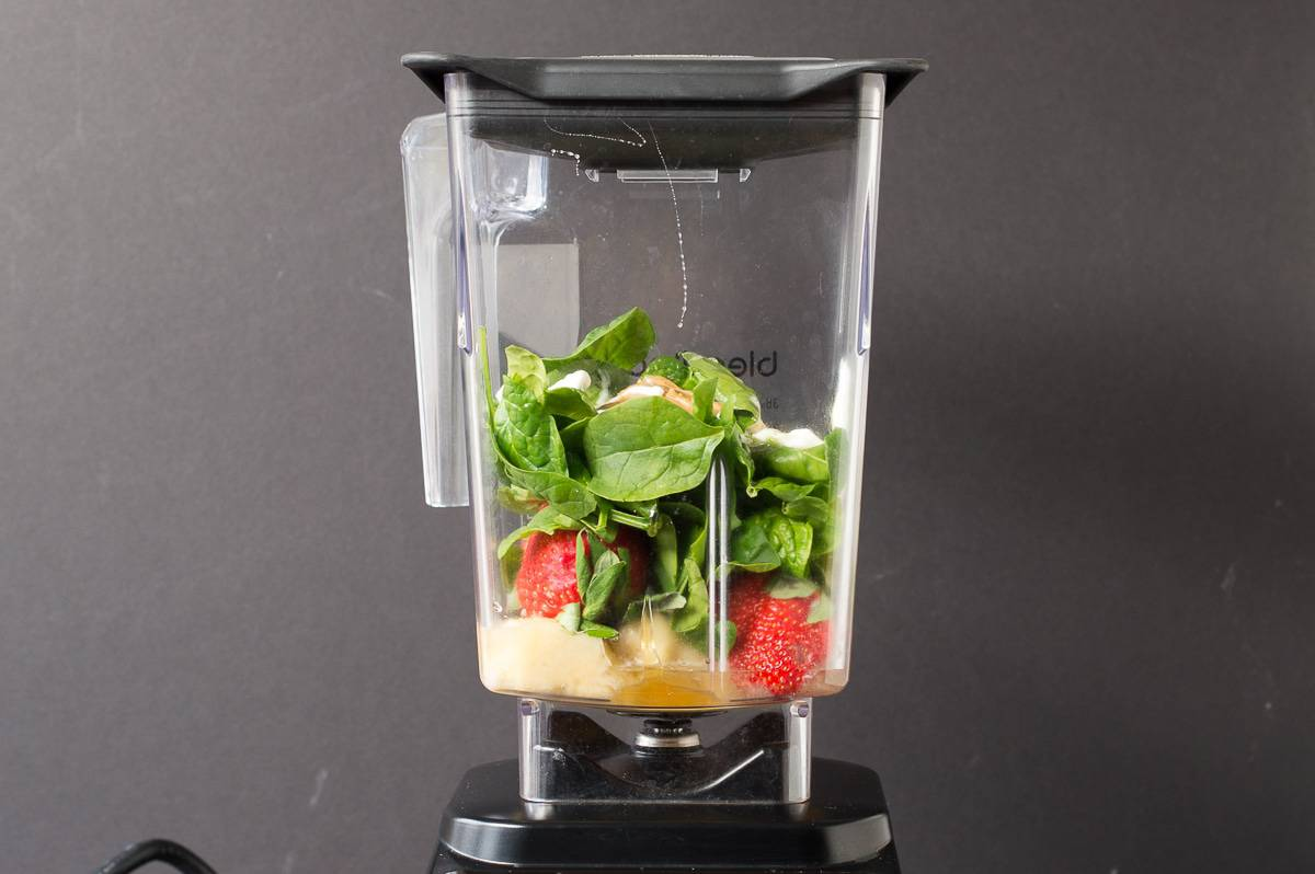 Spinach , banana and strawberries in a blender.
