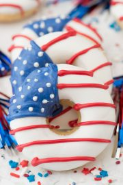 Three American Flag Donuts surrounded by red white and blue sprinkles.