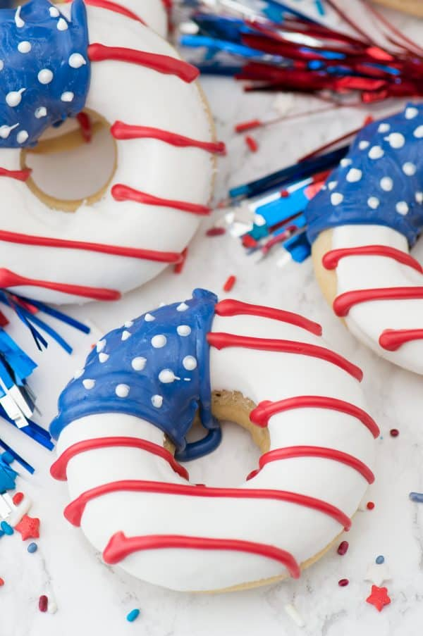 Three delicious American Flag Donuts surrounded by streamers.
