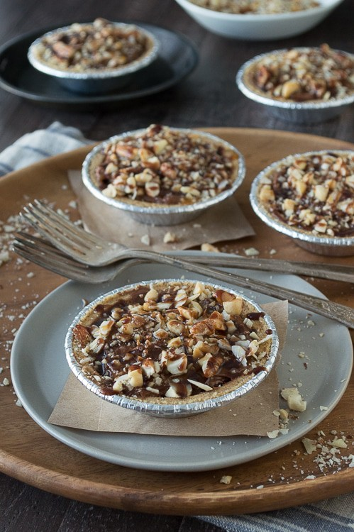 No bake mini pies with 2 layers of mixed nuts and a rich chocolate filling, all topped with chocolate and caramel!