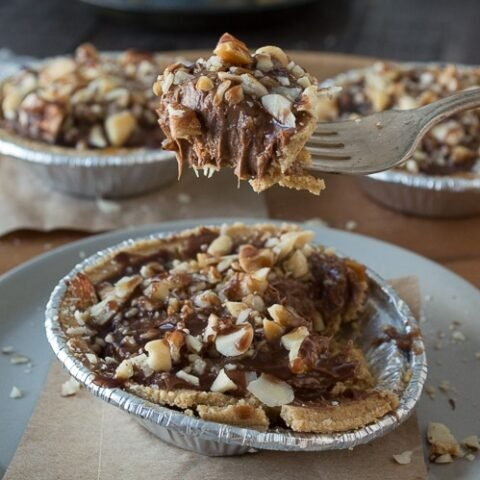 No bake mini pies with 2 layers of mixed nuts and a rich chocolate filling - top them with chocolate and caramel!