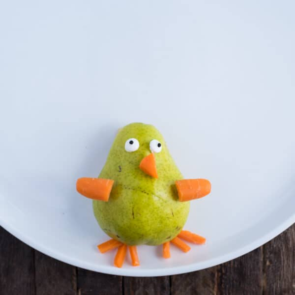 turkey fruit platter with pear for the turkey's body and carrots for the beak, wings, and legs