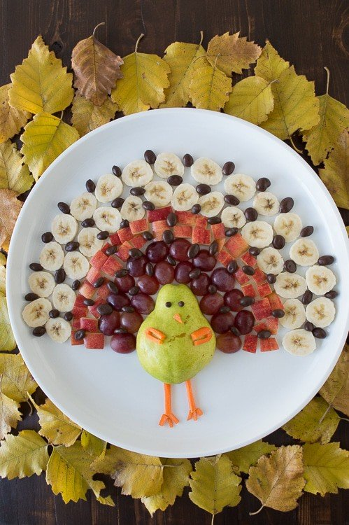 fruit platter in the shape of a turkey on a white serving tray