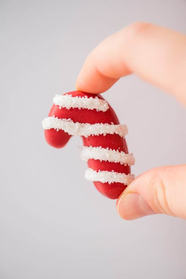fingers holding a candy cane shaped oreo ball on white background