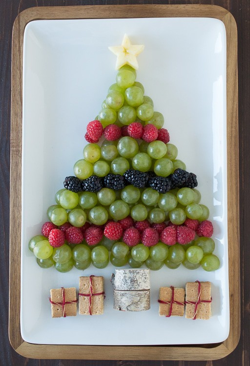 green grapes, raspberries and blackberries arranged to look like a Christmas tree on white platter