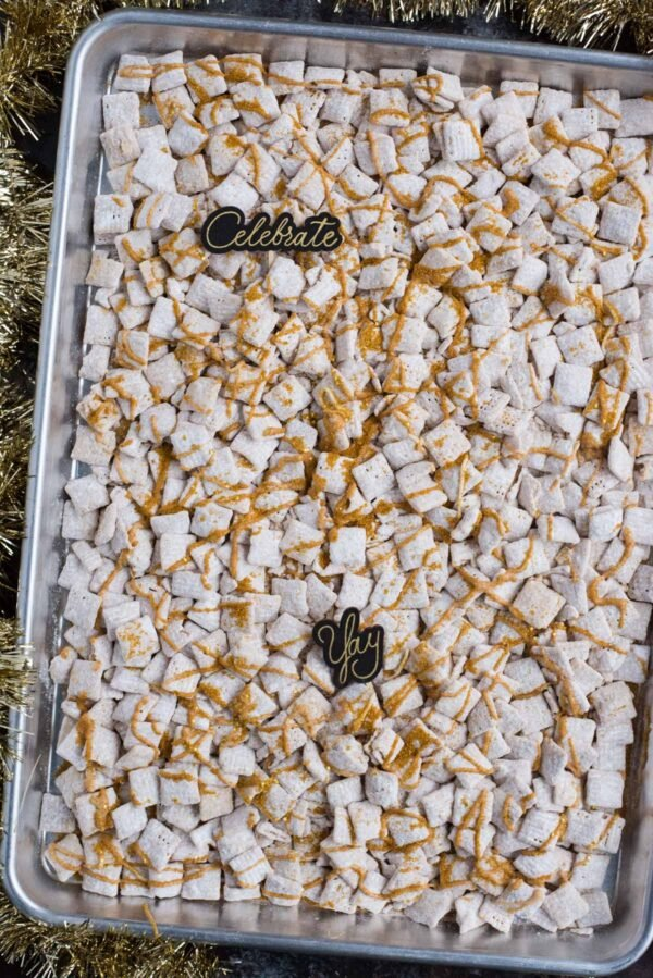 new year's eve white chocolate puppy chow with gold sprinkles and gold stars on a baking sheet