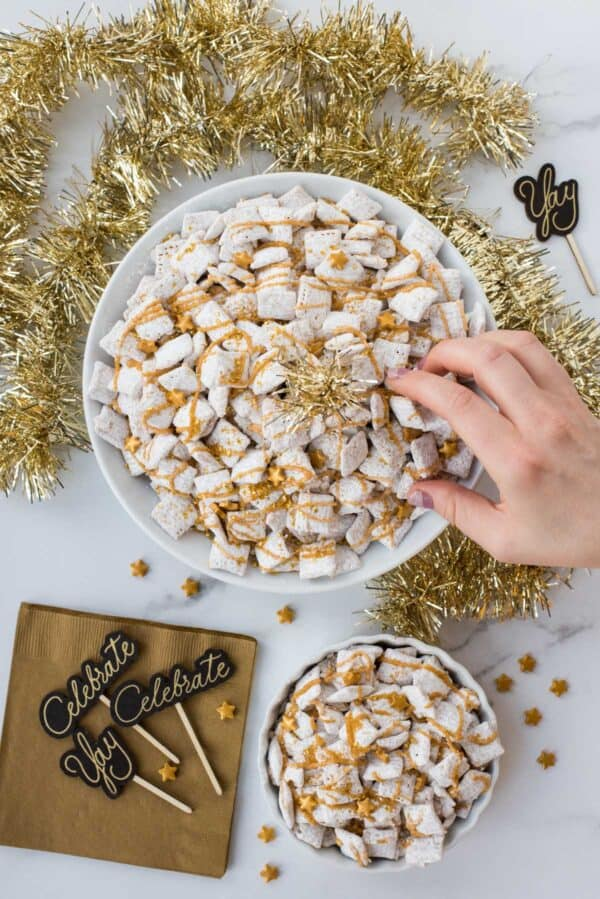 new year's eve white chocolate puppy chow with gold sprinkles and gold stars on a white background
