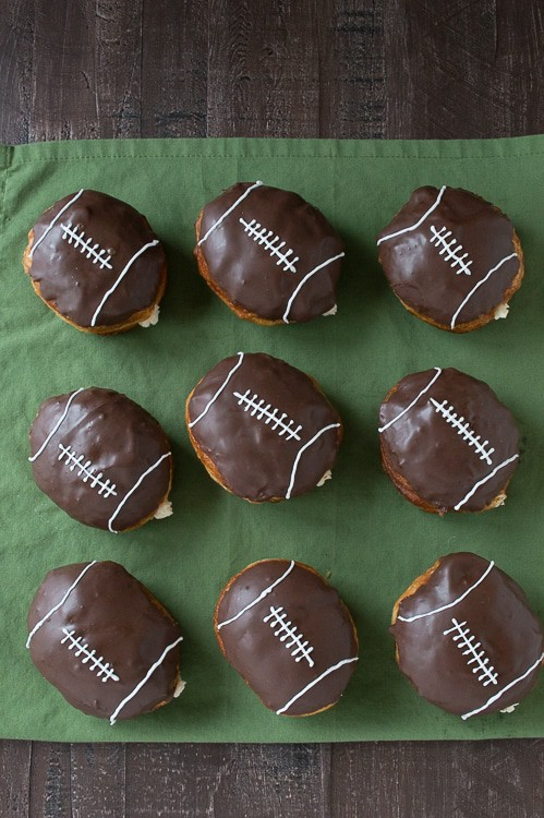 Cream Filled Chocolate Football Donuts - use refrigerated biscuits to make cream filled donuts! Decorate them to look like footballs for game day!