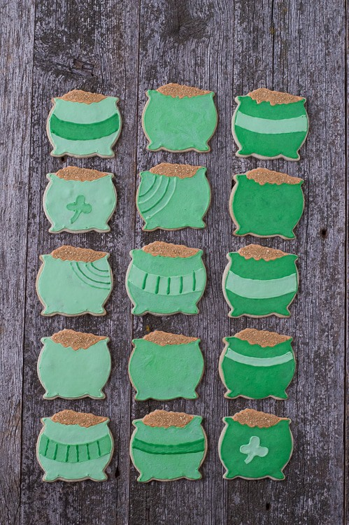 Fifteen homemade Pot o' Gold Cookies on a wooden table.