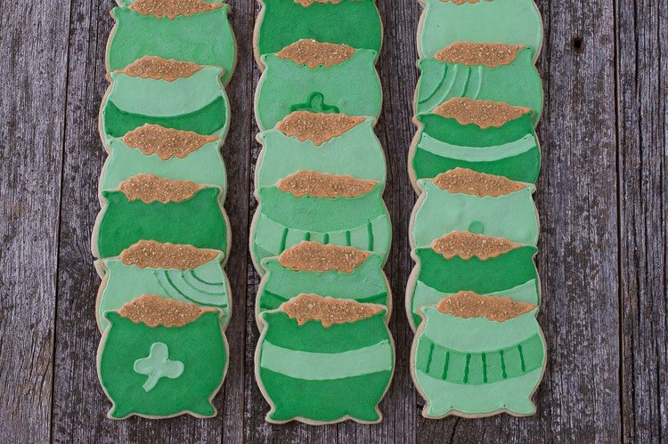 Eighteen homemade Pot o' Gold Cookies on a wooden table.