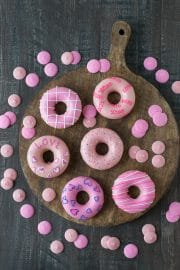 Six Valentine's Day Donuts on a wooden board surrounded by pink candy melts.