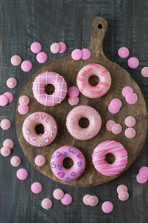 Delicious and cute Pink Valentine's Day Donuts on a wooden board surrounded by pink candy melts.