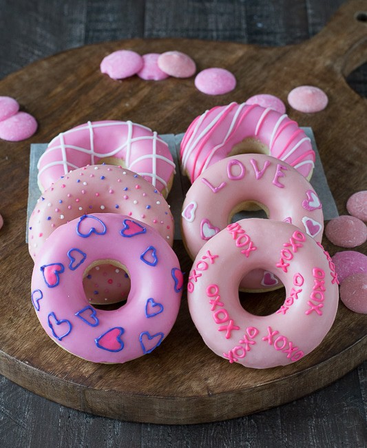 Six Valentine's Day Donuts covered in pink frosting on a wooden board.