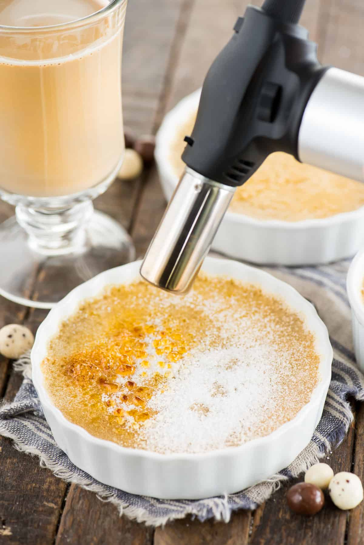 espresso creme brûlée in white round ramekin with blow torch crystalizing the sugar on top
