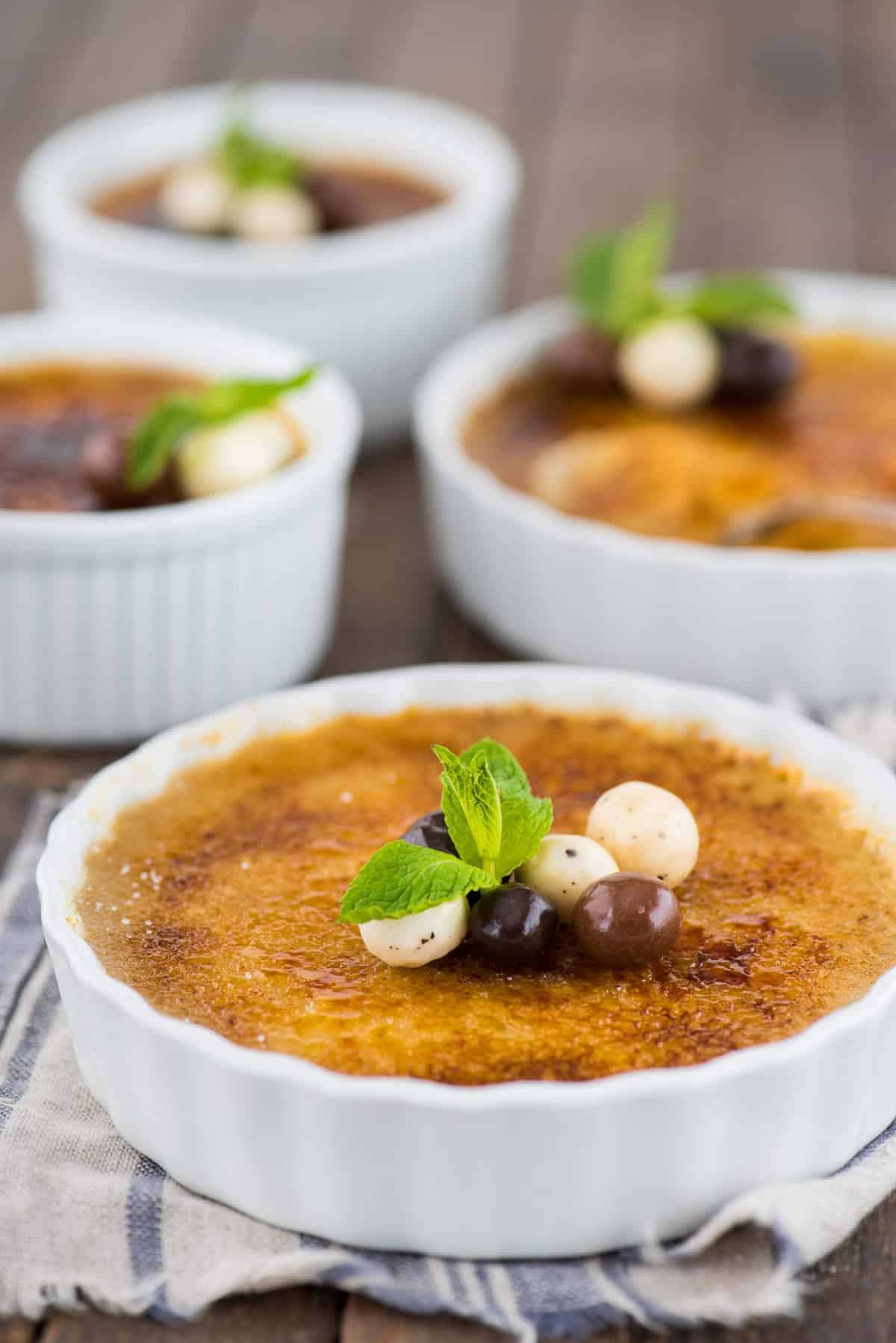 espresso creme brûlée in white round ramekin with chocolate covered coffee beans and mint leaf on top of creme brûlée