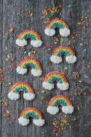 Eight Rainbow Sugar Cookies decorated with Fruity Pebbles and coconut shavings on a wooden table.