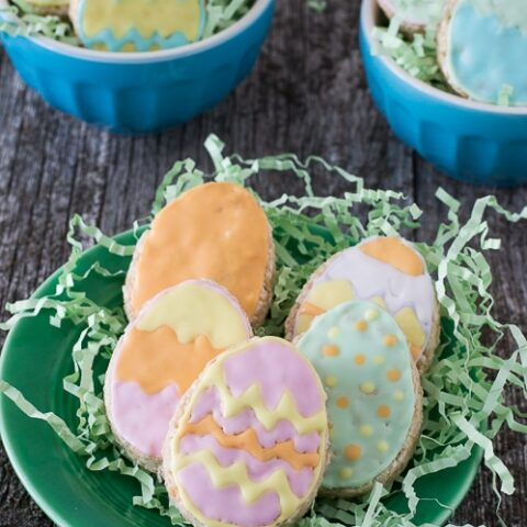 Five Rice Krispies Easter Eggs on fake green grass on top of a green serving plate on a wooden table.