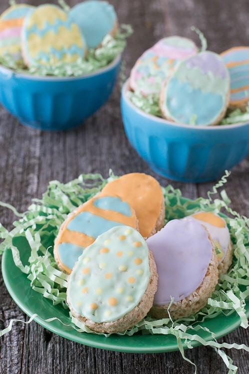 Five Rice Krispies Easter Eggs with colorful royal icing on a green serving plate on a wooden table.