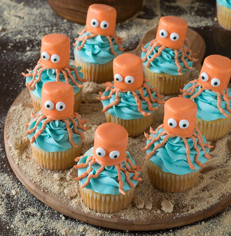Eight east Octopus Cupcakes covered in blue buttercream frosting arranged on a round wooden board.