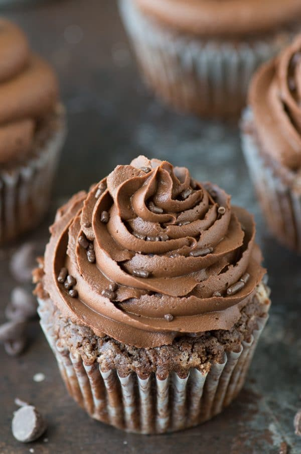 From scratch chocolate cupcakes with chocolate buttercream and delicious chocolate sprinkles on a counter.