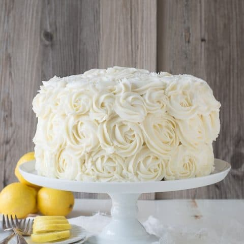 Homemade Lemon Layer Cake with Lemon Buttercream Rosettes on a white cake platter.