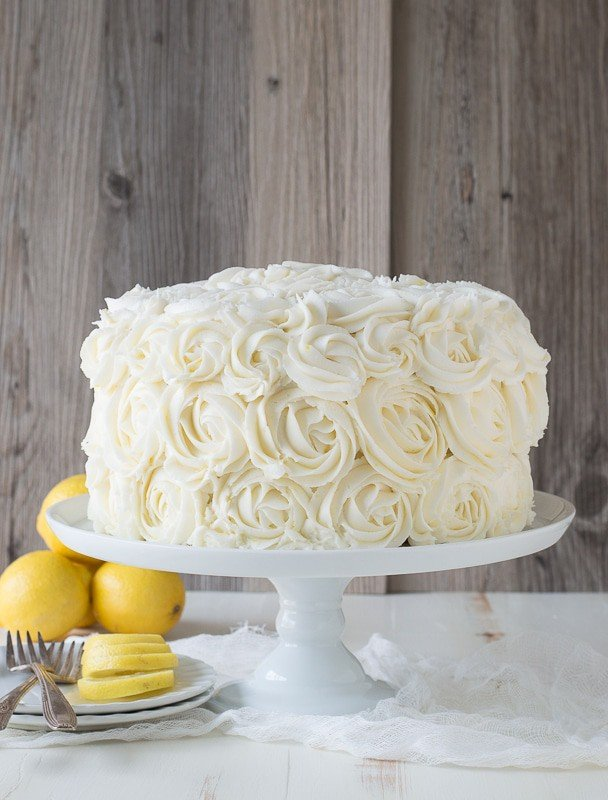 Beautiful Lemon Layer Cake with Lemon Buttercream Rosettes on a white cake platter.