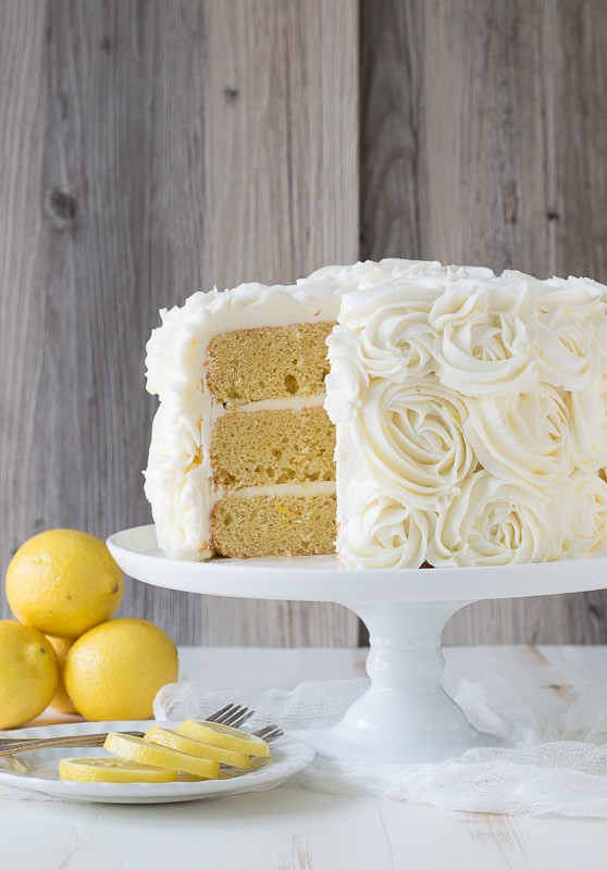 Slice missing out of Lemon Layer Cake on a white cake platter.