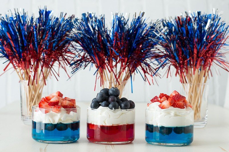 blue and red jello in glass cups topped with whipped cream and chopped strawberries and blueberries