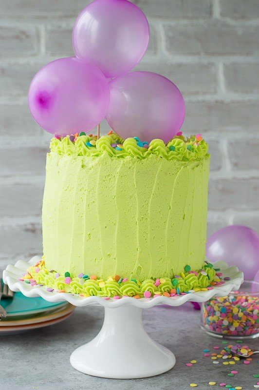 Homemade funfetti cake with lime green buttercream! Top the cake with a DIY balloon cake topper!