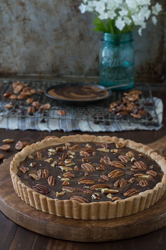 This turtle tart is swirled with caramel and chocolate then topped with pecans and sea salt!