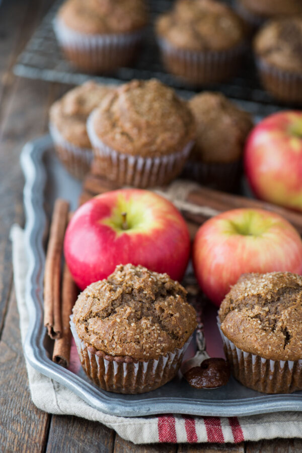 apple butter muffins on metal serving tray with apples and tan and red striped towel