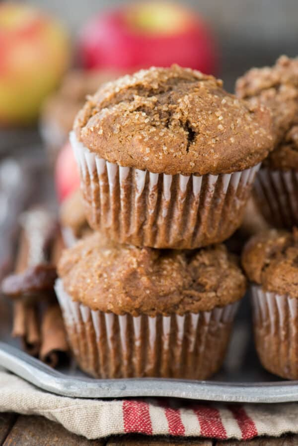 apple butter muffins stacked on each other on metal serving tray with apples and tan and red striped towel