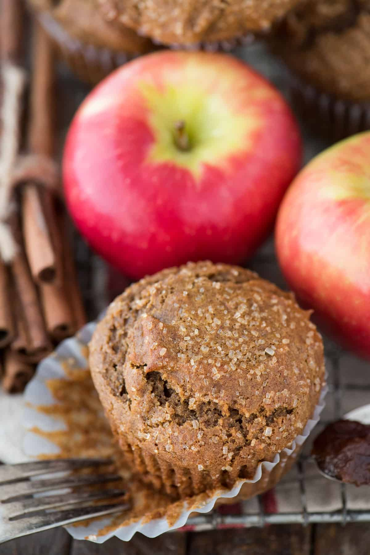 apple butter muffins on cooling rack with apples and cinnamon sticks